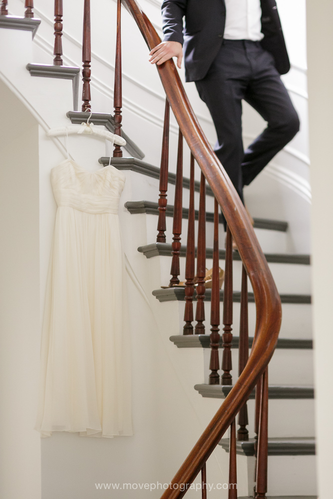A wedding dress hangs from stairs in a Mendocino farmhouse before a California coast wedding.