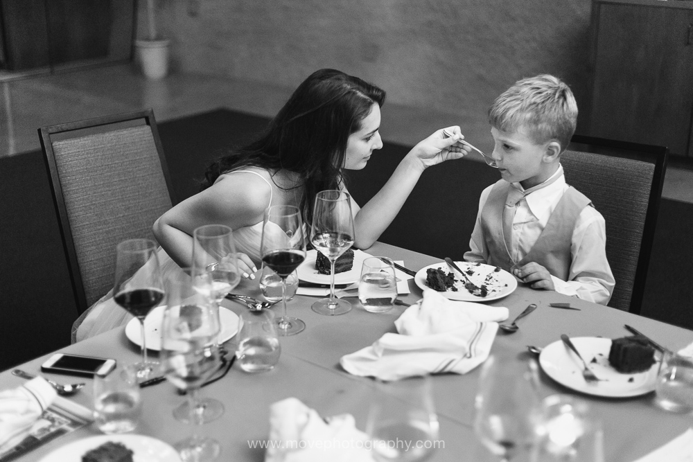 A photograph of a bride feeding wedding cake to a young ringbearer in a suit.