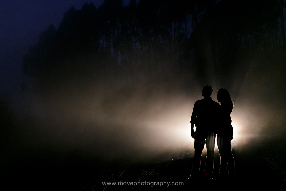 A fiancée and her fiance stand in the glow of their car's headlights in the Oakland hills at twilight, in front of eucalyptus and the blue glow of the sky, after their Rockridge engagement session.