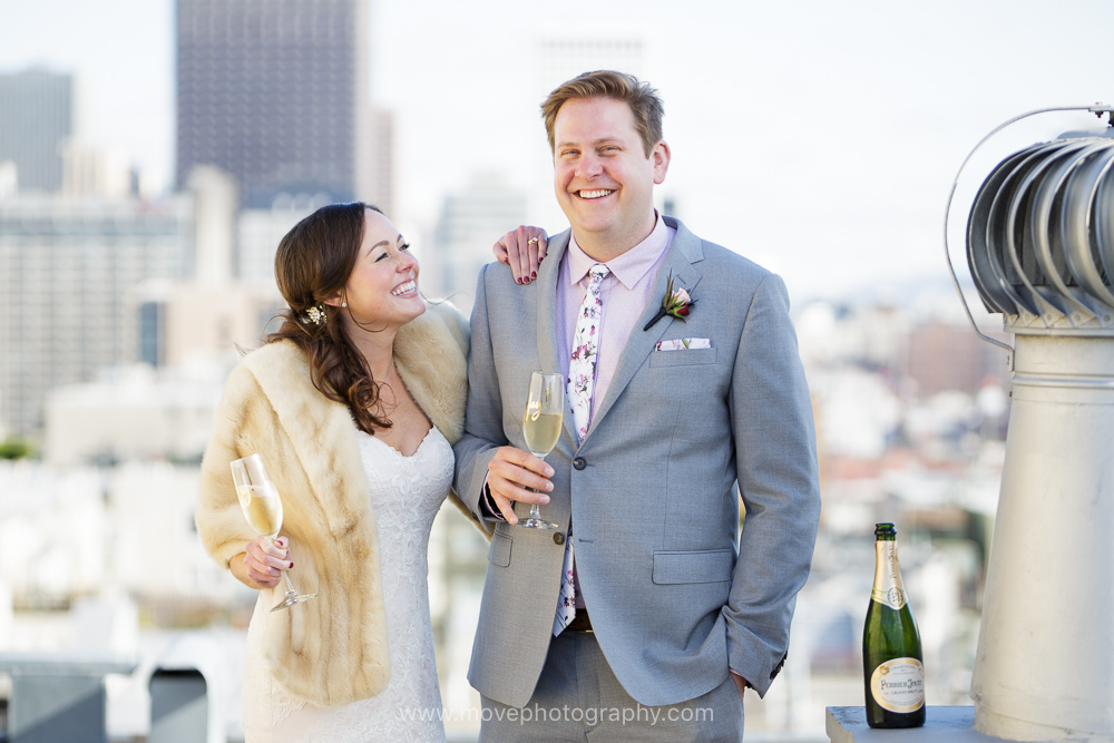 A bride and groom enjoy a glass of champagne on a rooftop in San Francisco's iconic North Beach neighborhood after their San Francisco wedding.