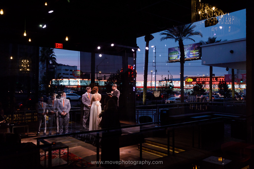 A wedding party stands at the altar at the Sayers Club, in the SLS Las Vegas. Visible in the reflection are the neon lights and marquees of the Las Vegas strip. This SLS Las Vegas wedding took place in the spring.